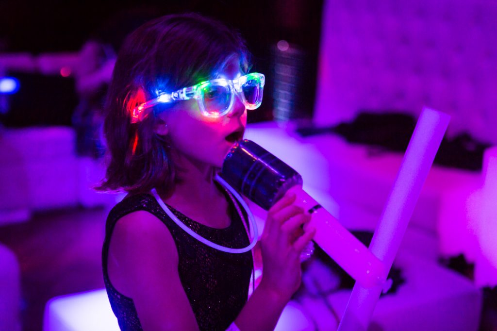 Kid with lit up glasses at a bat mitzvah for an article on 'How to Find a Venue'