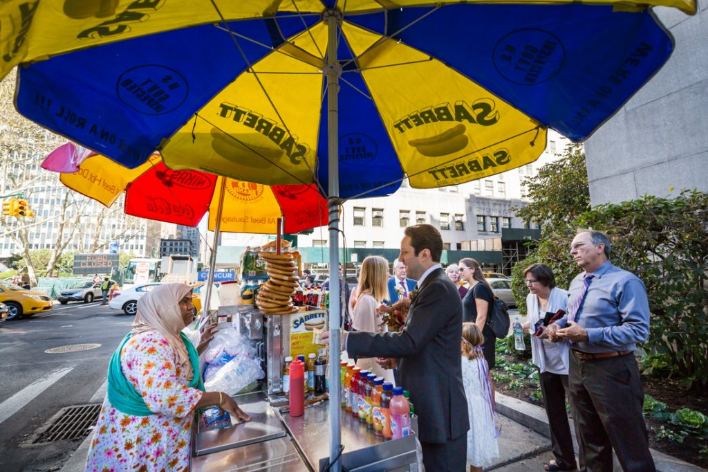 Groom buying water at a hot dog stand for an article on How to Get Married at City Hall in Any NYC Borough
