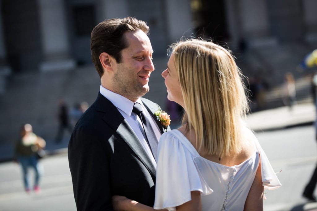 Bride and groom looking at each other for an article on How to Get Married at City Hall in Any NYC Borough