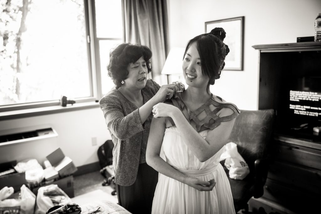 Black and white photo of mother attaching cape to bride at a Bear Mountain Inn wedding