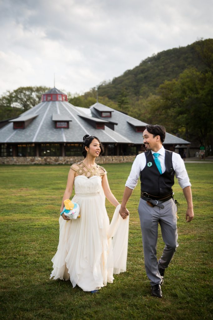 Bride and groom walking hand in hand away from carousel at a Bear Mountain Inn wedding