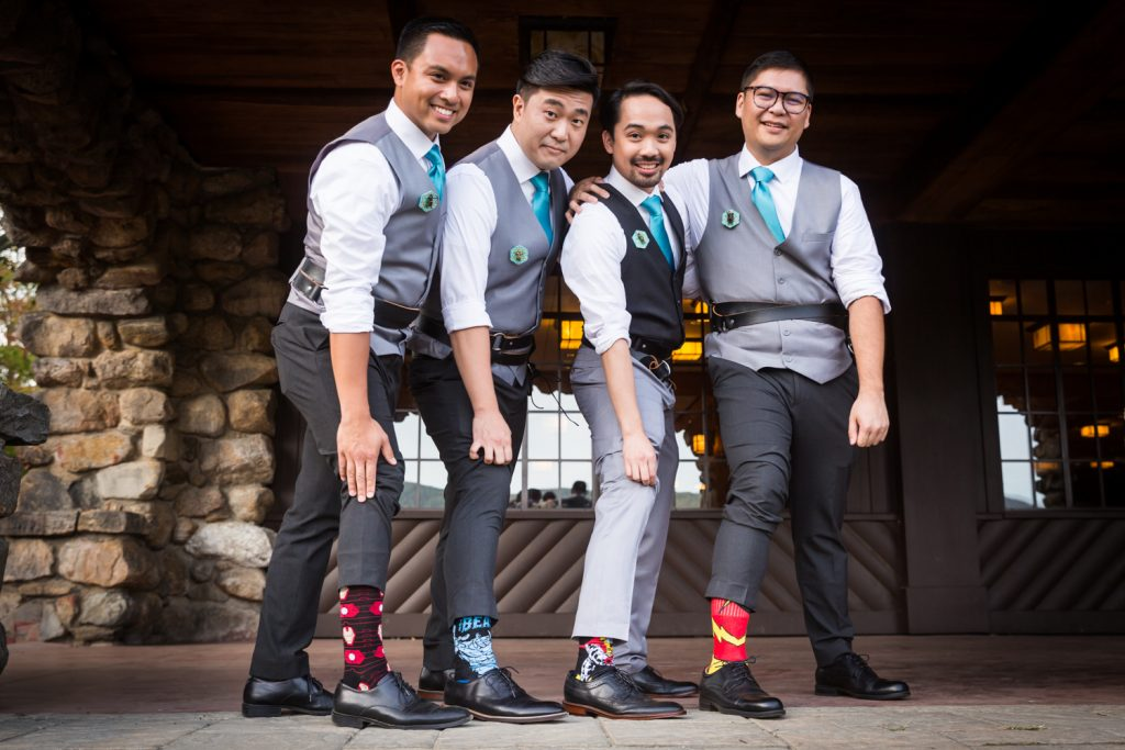 Groom and groomsmen holding up pants to reveal socks at a Bear Mountain Inn wedding