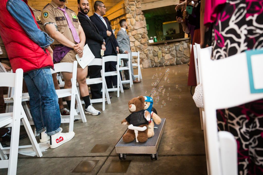 Two teddy bears on a cart moving down aisle with bubbles blowing at a Bear Mountain Inn wedding