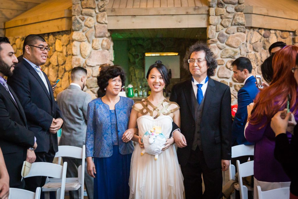Bride walking down aisle escorted by both parents at a Bear Mountain Inn wedding