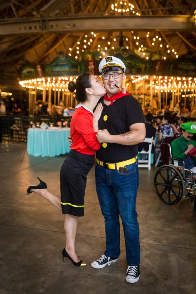 Woman dressed as Olive Oyl kissing man dressed as Popeye on the cheek at a Bear Mountain Inn wedding