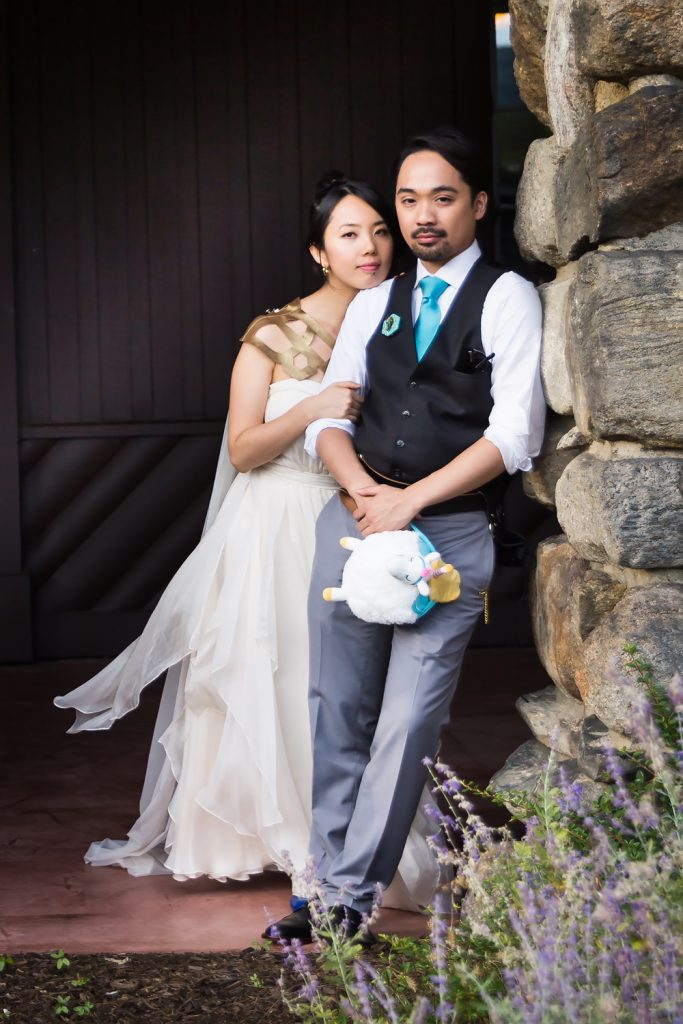 Bride and groom leaning against stone wall at a Bear Mountain Inn wedding