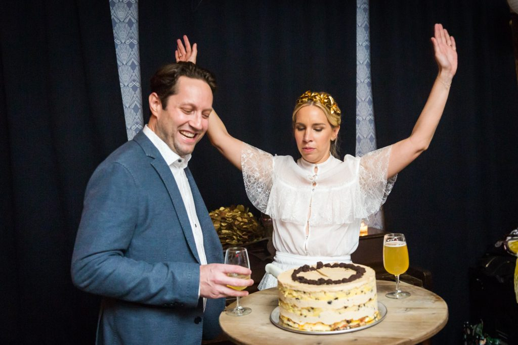 Bride cheering with hands up after cutting wedding cake