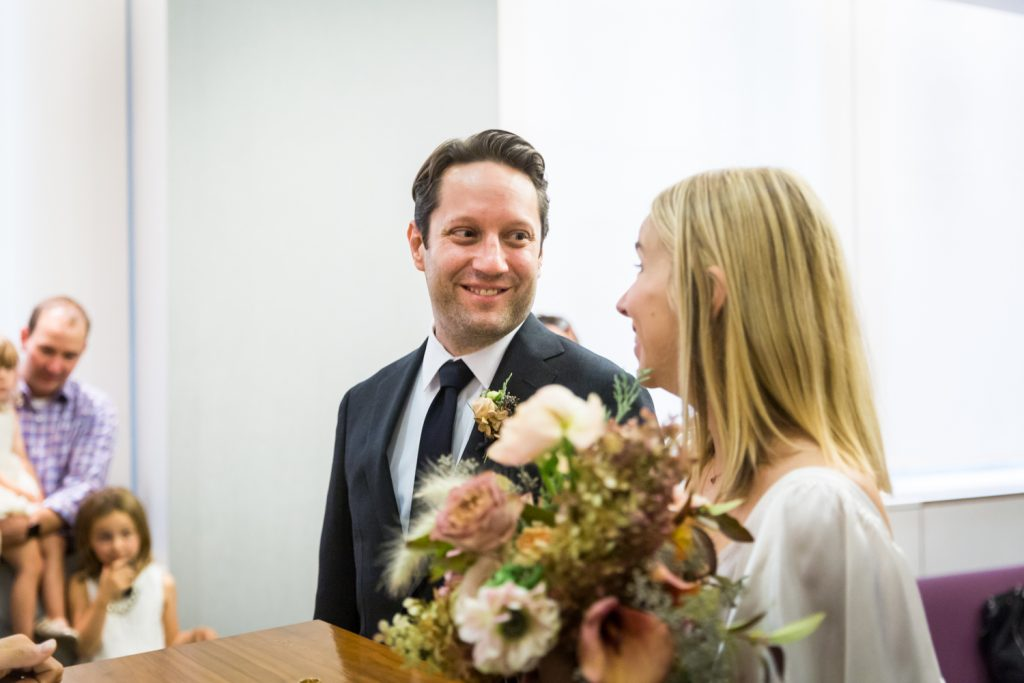 Groom looking at bride for an article on How to Get Married at City Hall in Any NYC Borough