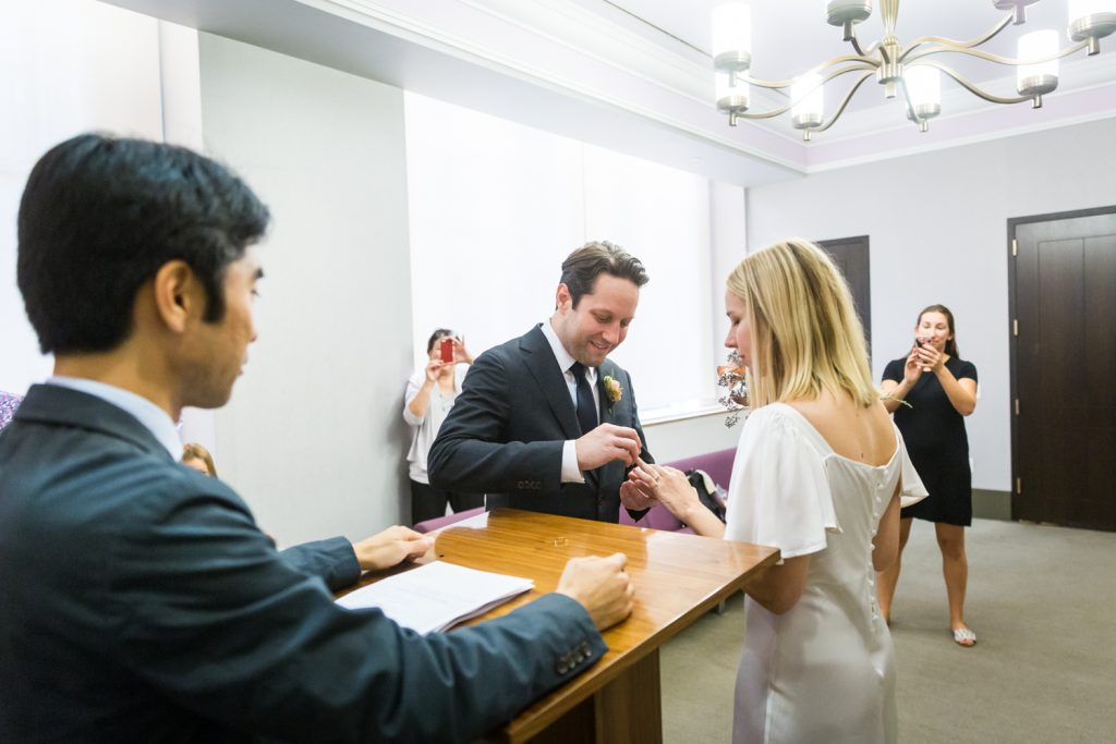 Bride and groom exchanging rings for an article on How to Get Married at City Hall in Any NYC Borough