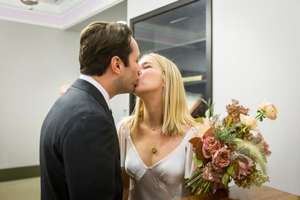 Bride and groom kissing for an article on How to Get Married at City Hall in Any NYC Borough