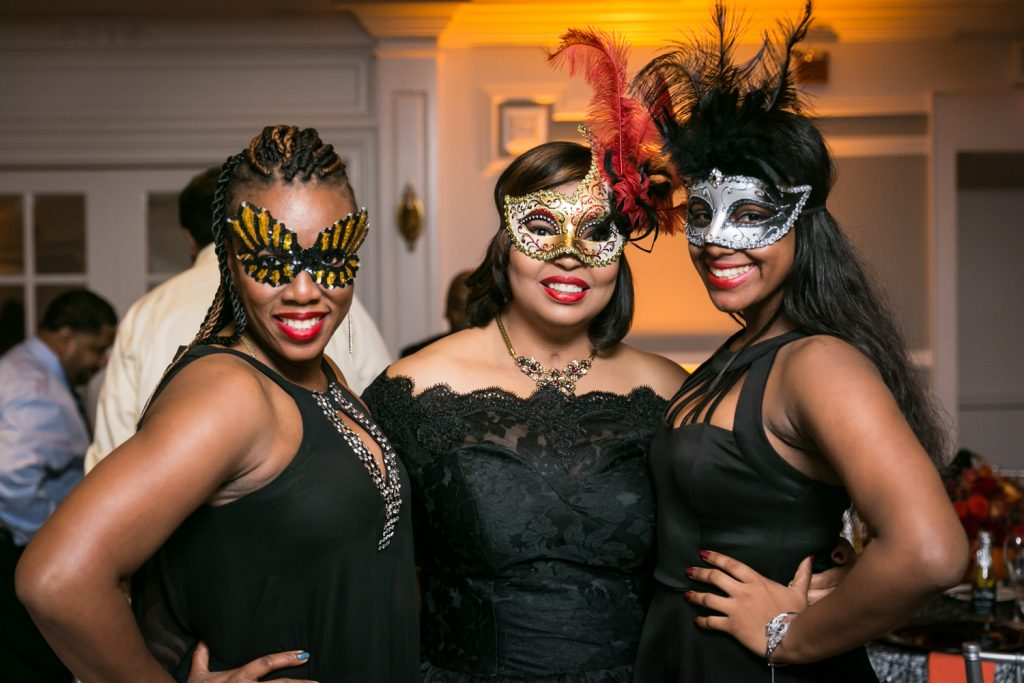 Three women dressed in masks for an article on how to plan a Halloween wedding
