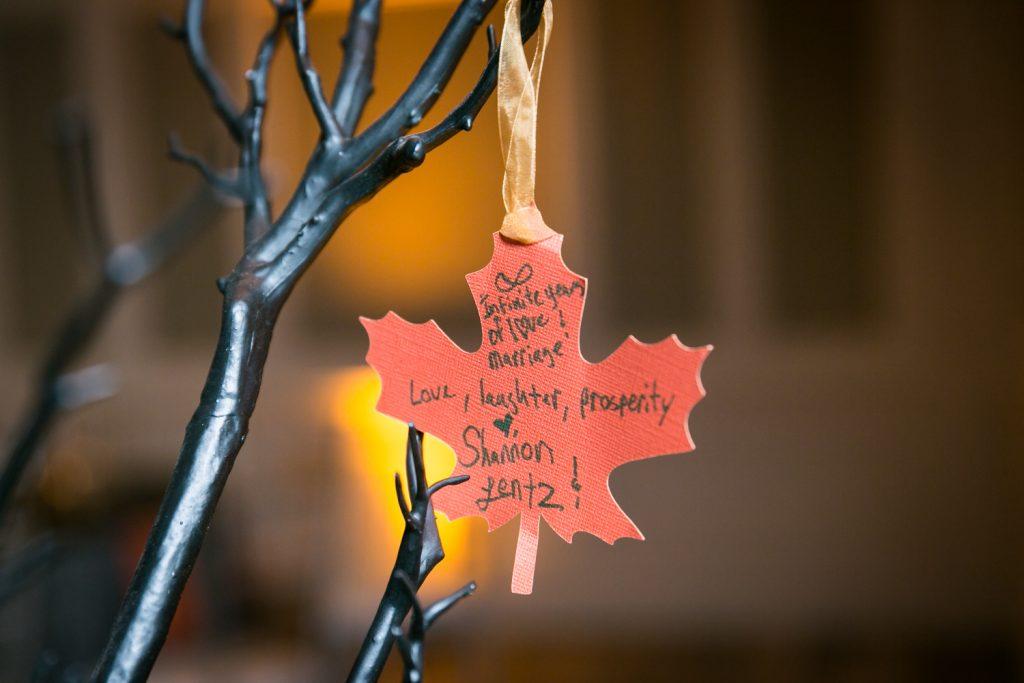 Orange leaf of a wishing tree at a Halloween-themed wedding reception