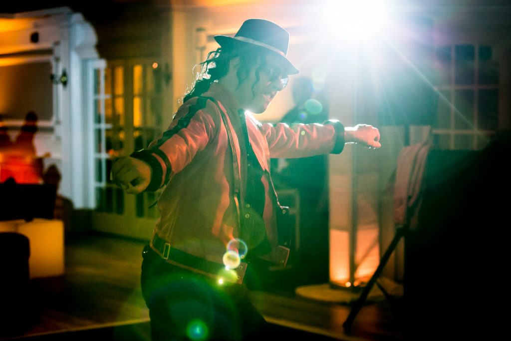 Michael Jackson impersonator dancing in front of spotlight