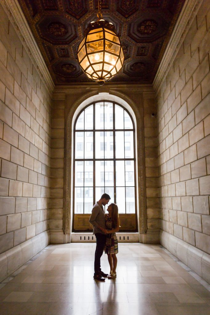 Couple in front of a window for a New York public library engagement shoot