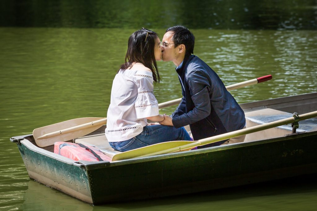 Man and woman kissing in boat after Central Park Lake proposal