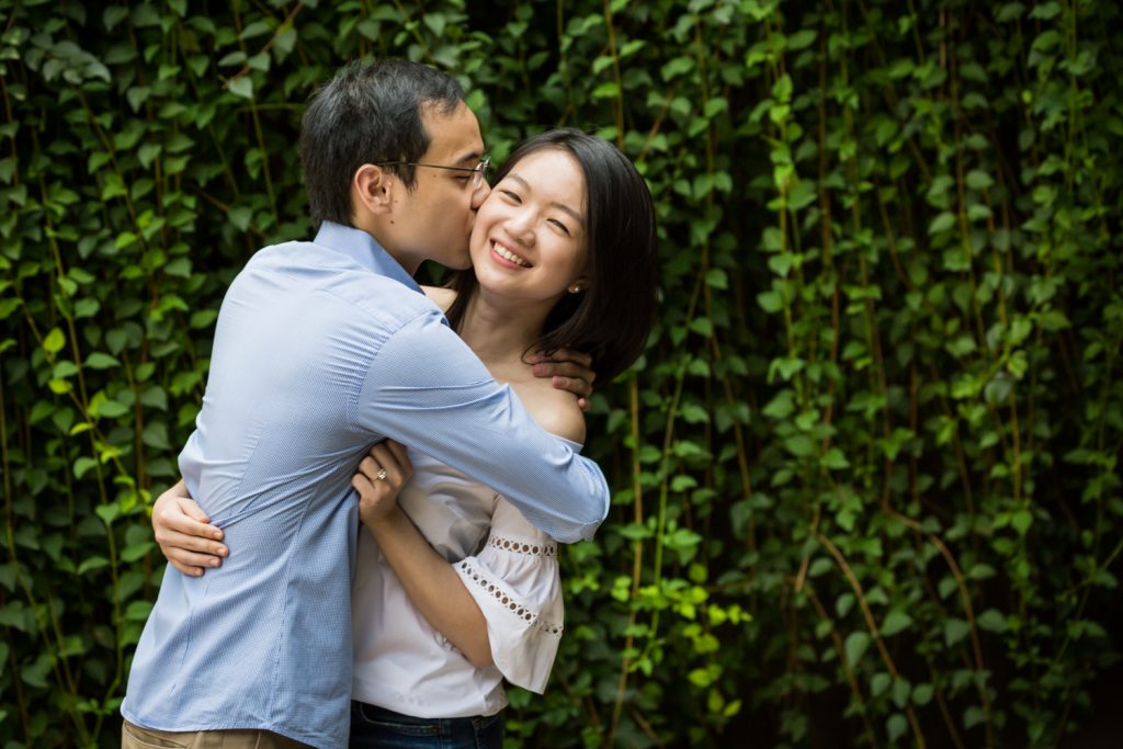 Engagement portrait of man kissing woman in front of ivy wall after Central Park Lake proposal