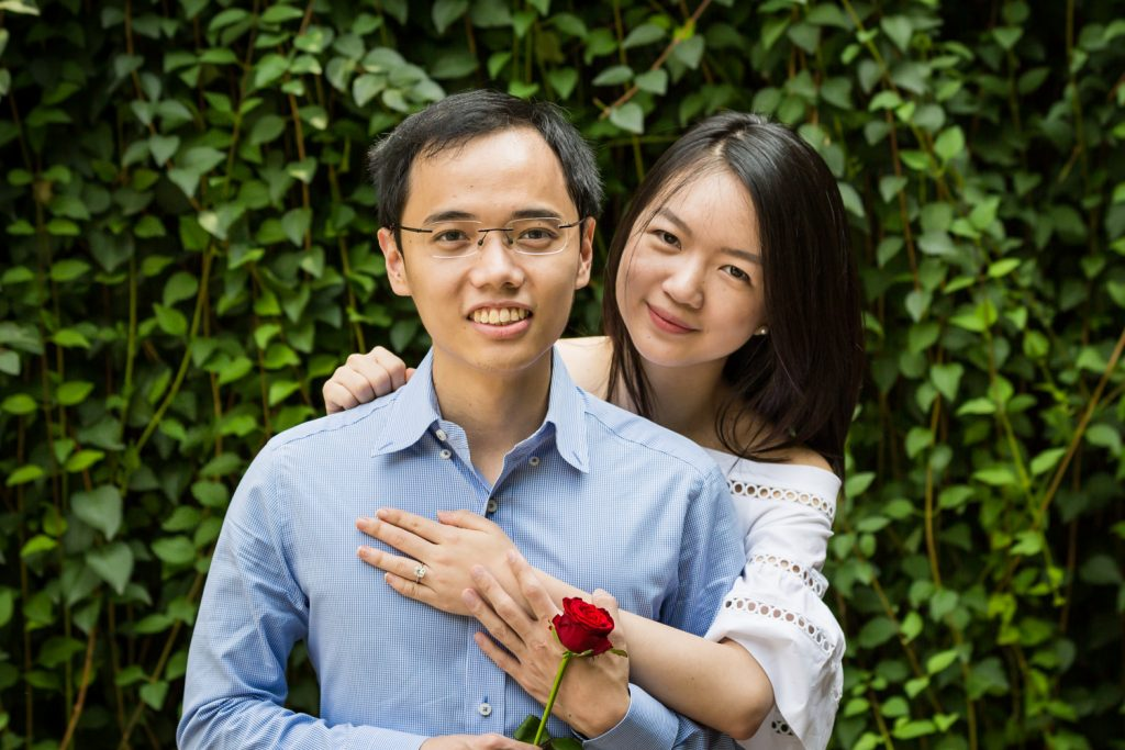Engagement portrait of couple in front of ivy-covered Trefoil Arch after Central Park Lake proposal