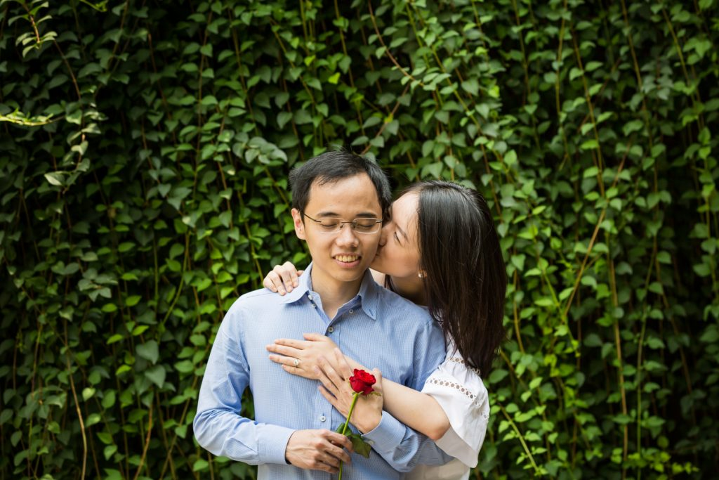 Engagement portrait of woman kissing man in front of ivy-covered Trefoil Arch after Central Park Lake proposal