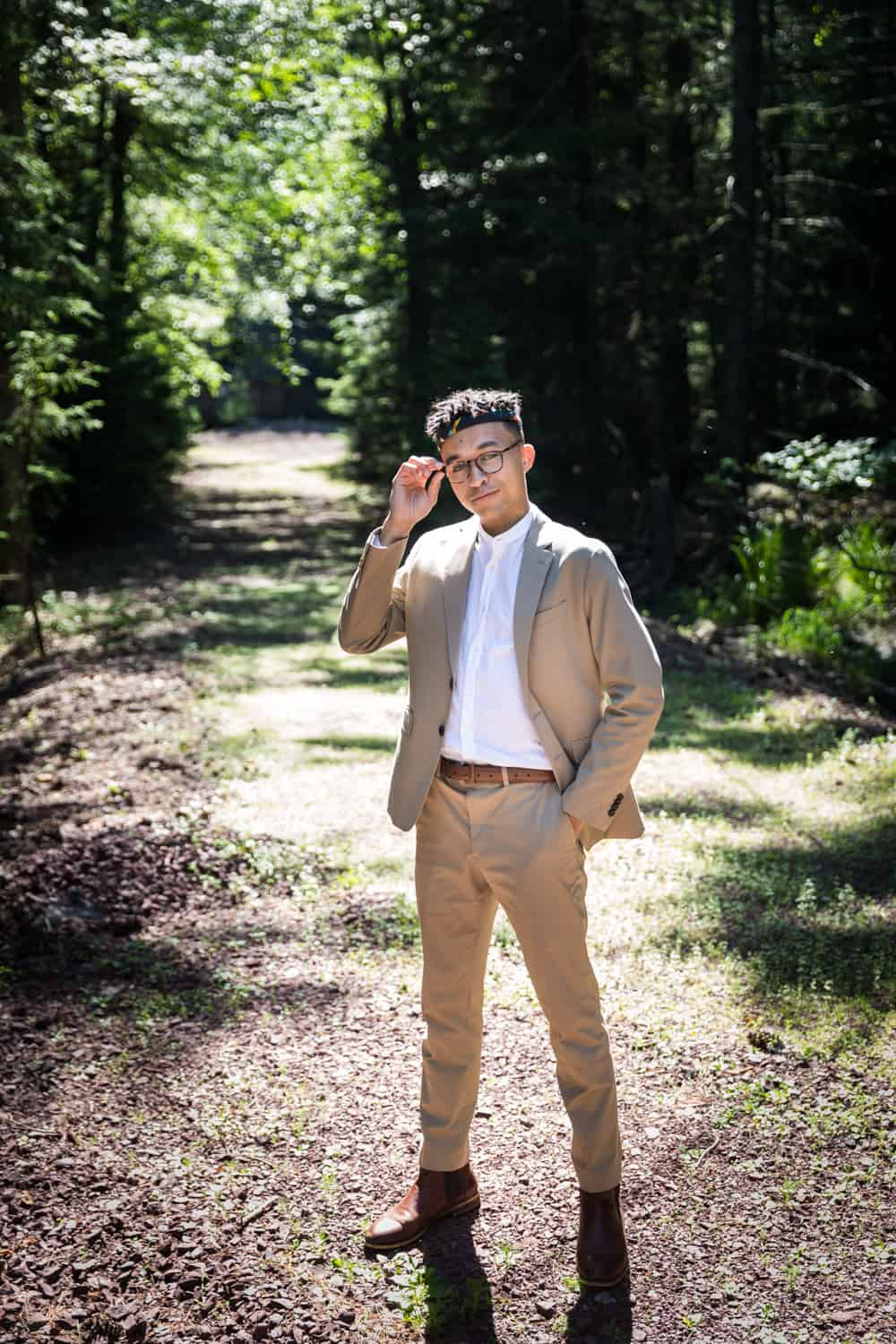 Young man wearing tan suit and touching glasses in woods