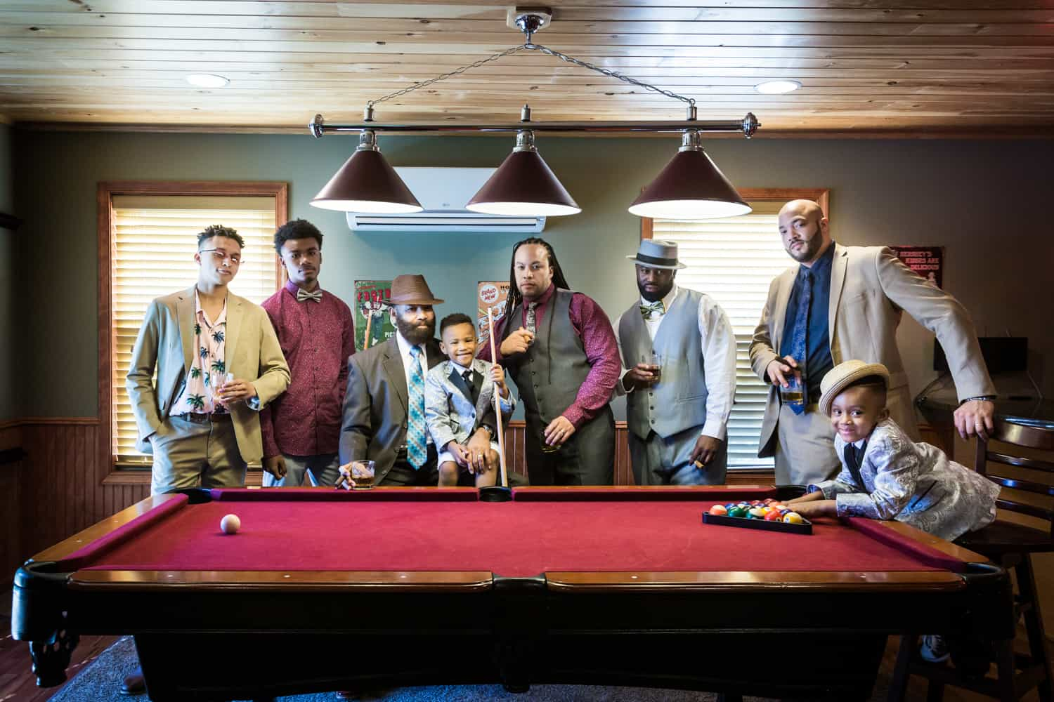 Male family members behind a pool table during a family reunion portrait
