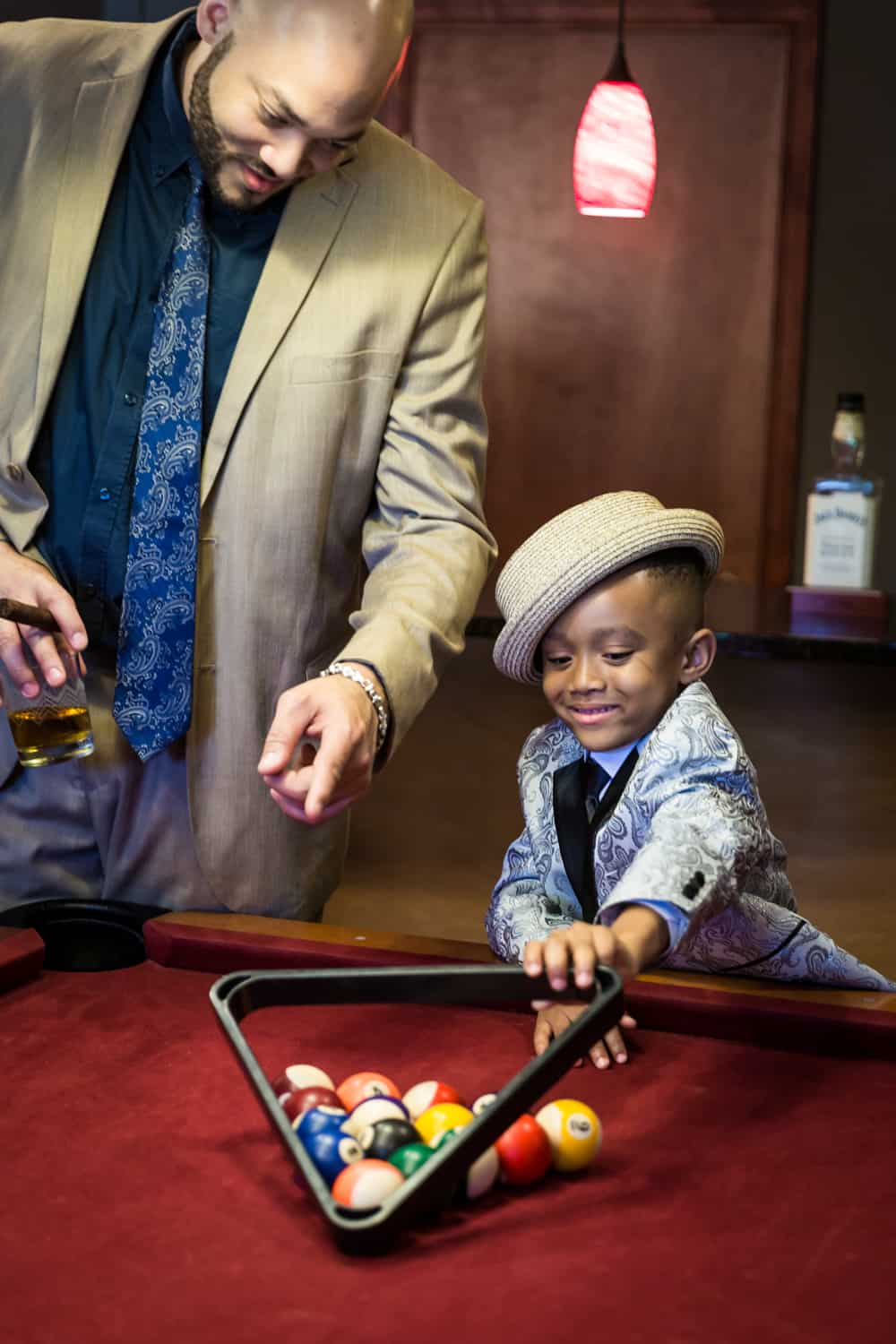 Man helping little boy learn to rack pool balls during a family reunion portrait