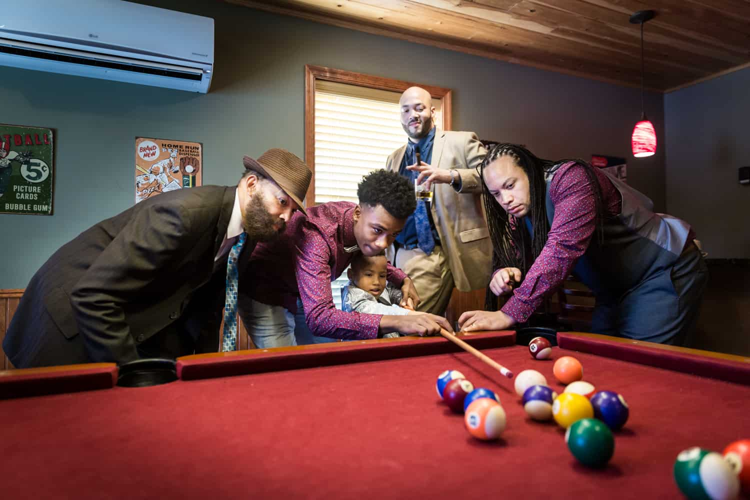 Male family members helping a little boy play pool during a family reunion portrait