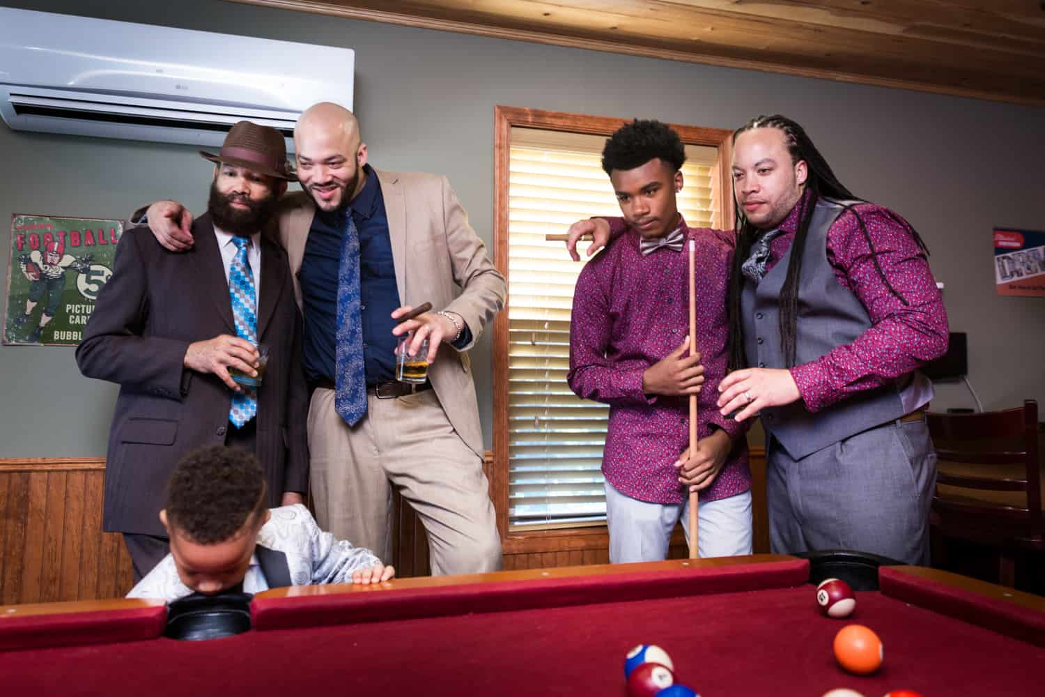 Male family members watching pool table during a family reunion portrait
