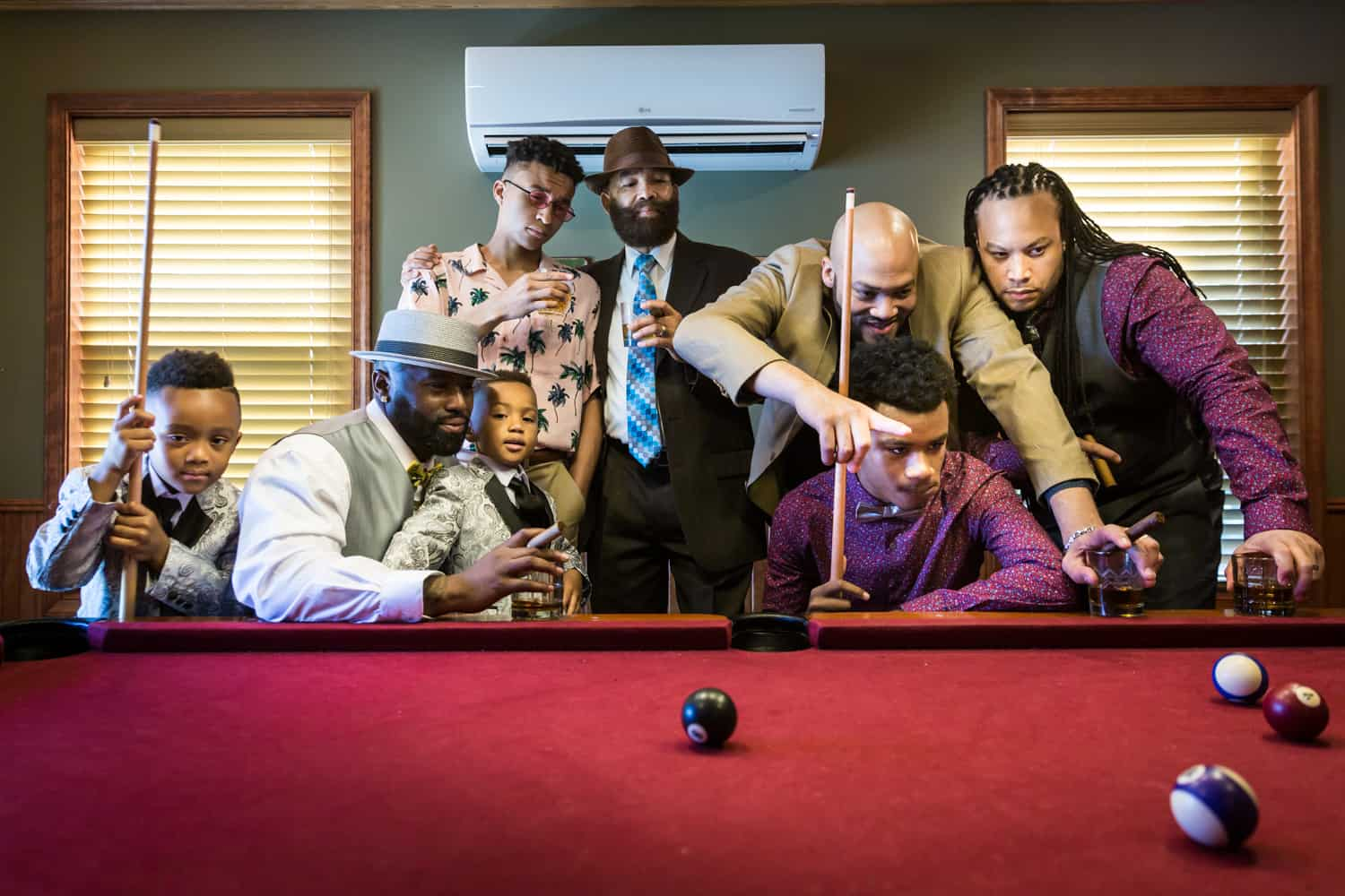 Male family members helping little boys play pool during a family reunion portrait