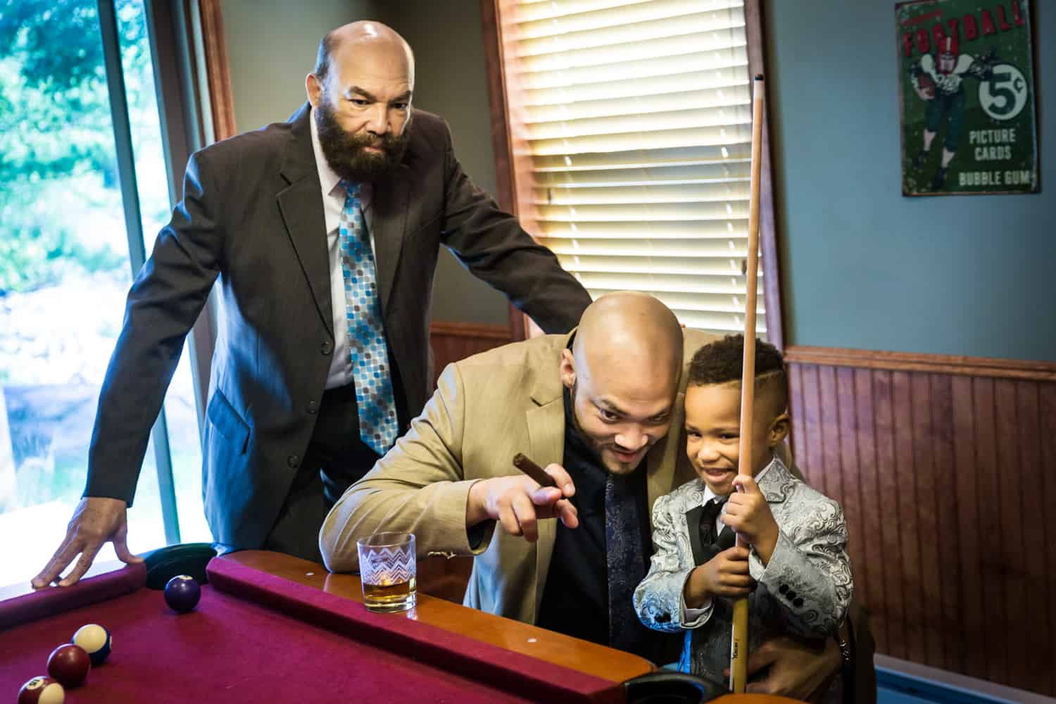 Two male family members helping little boy play pool during a family reunion portrait