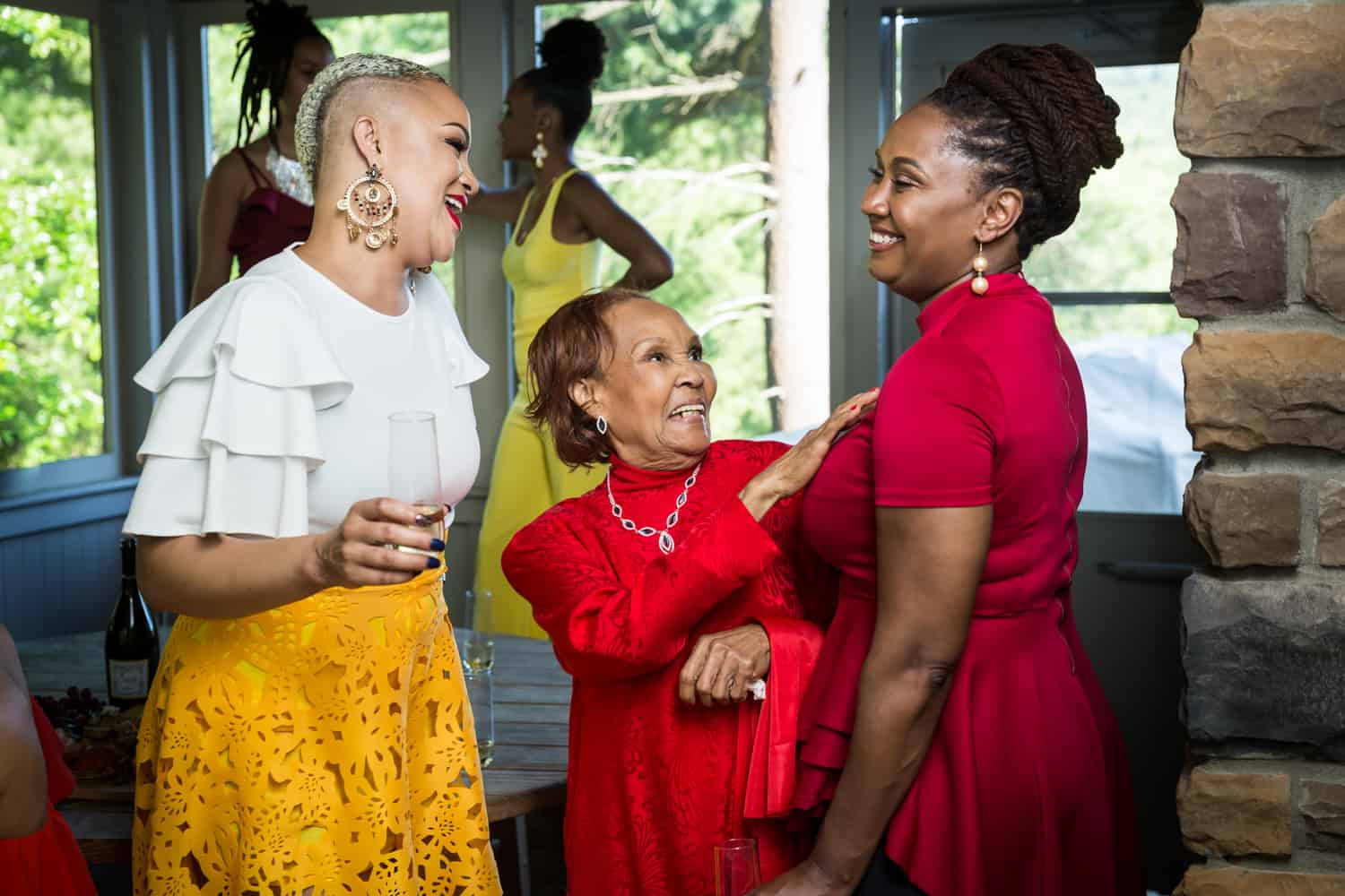 Three female family members laughing during a family reunion portrait