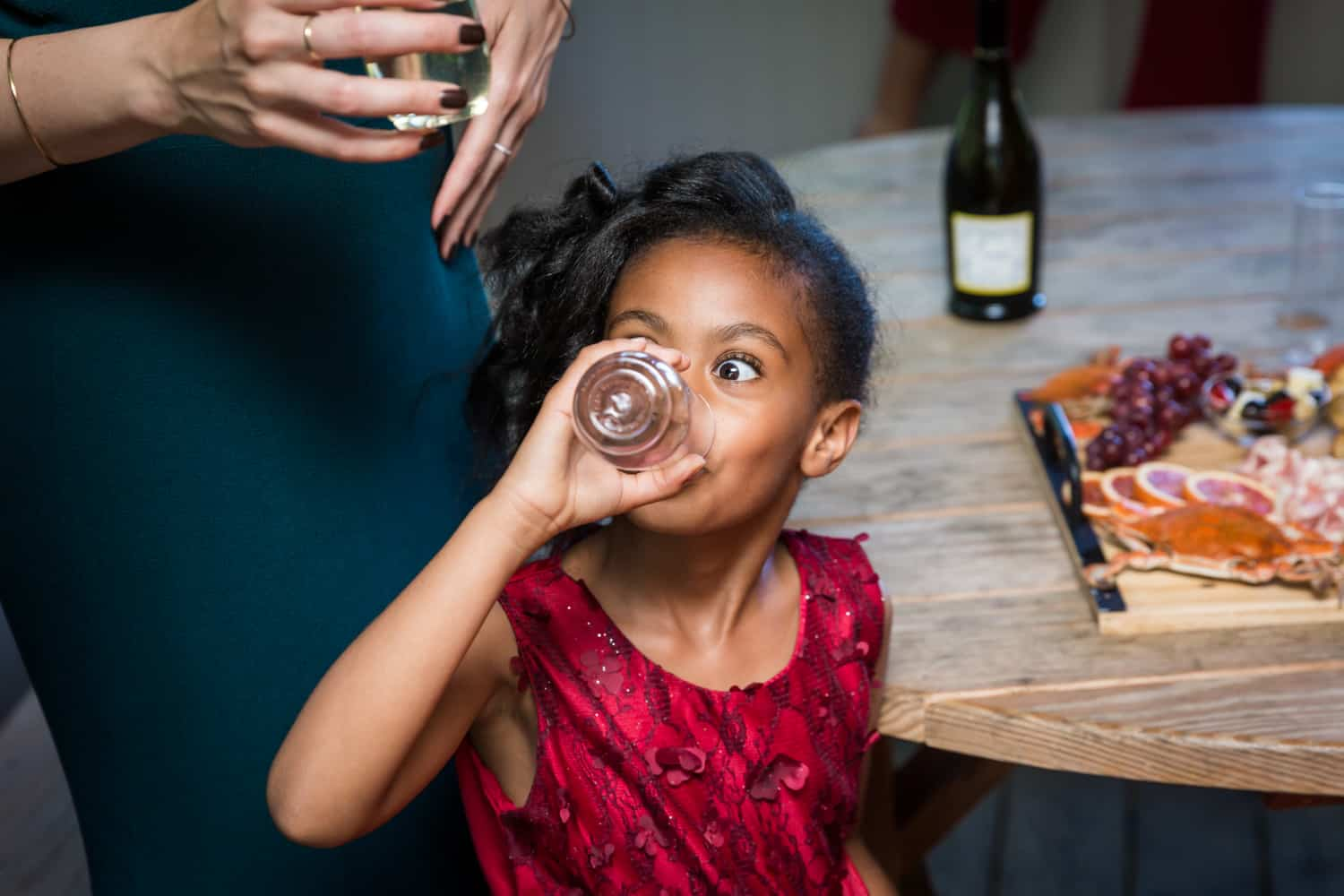 Little girl drinking from glass during a family reunion portrait