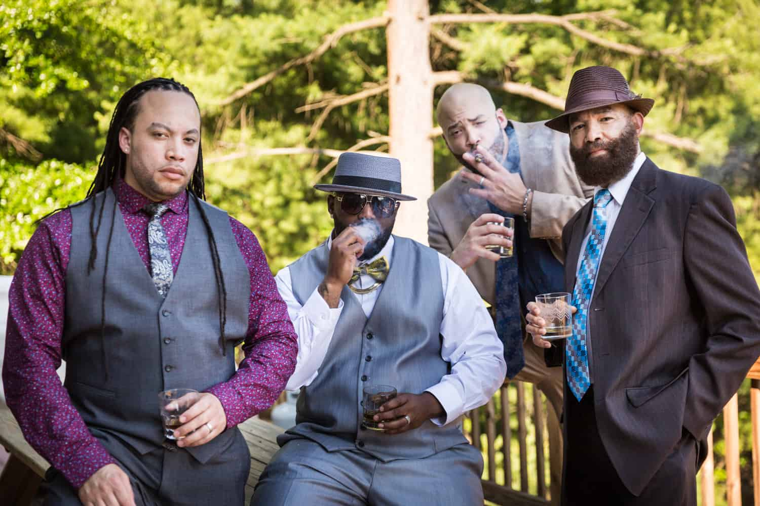 Male family members smoking together on porch during a family reunion portrait