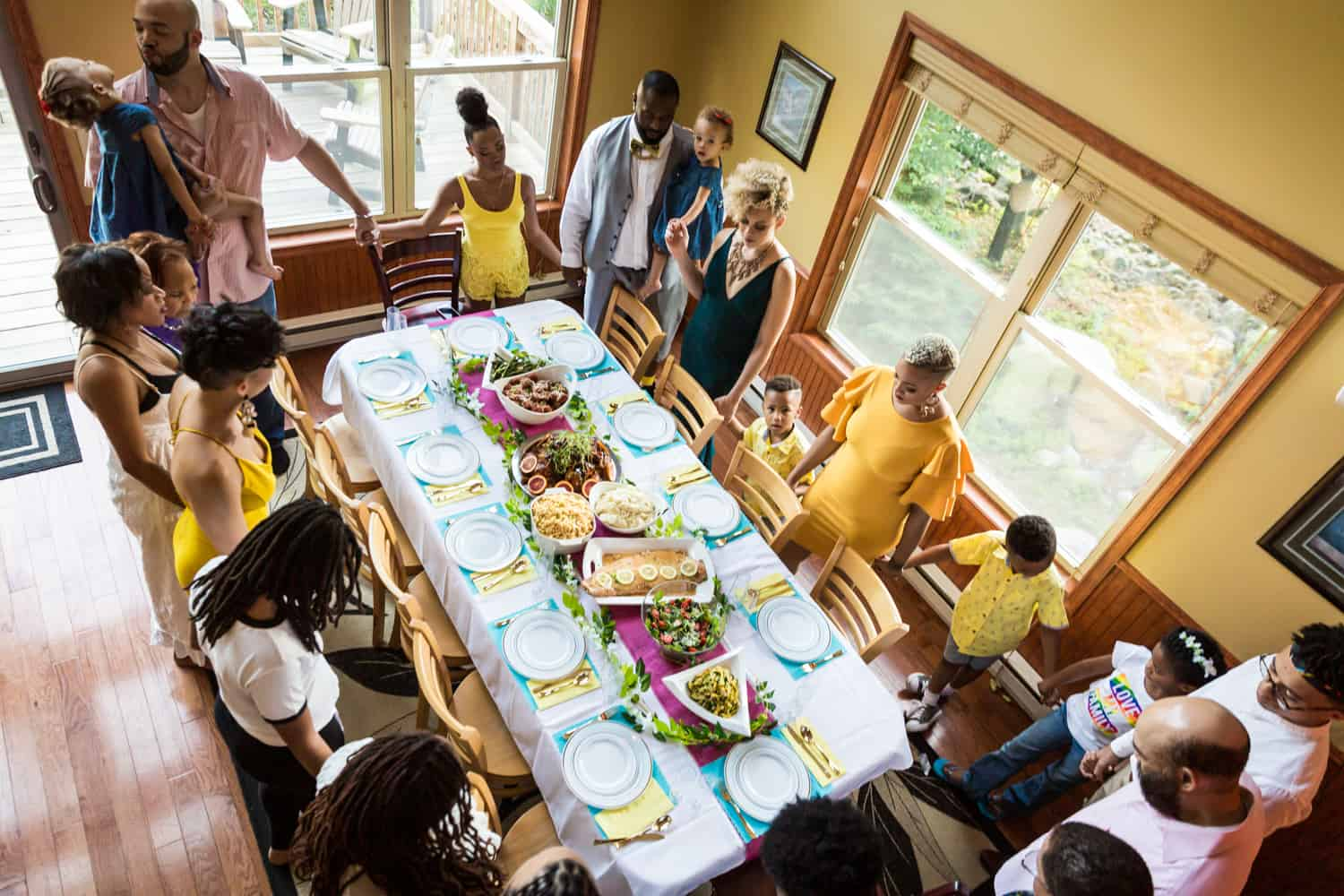 Family holding hands and praying around dinner table during a family reunion portrait