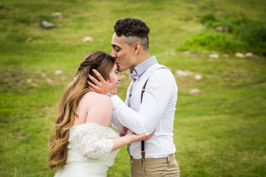 Groom kissing top of bride's head