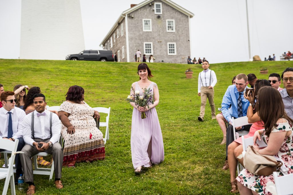 Bridesmaid walking down the aisle for an article on Montauk Lighthouse wedding tips