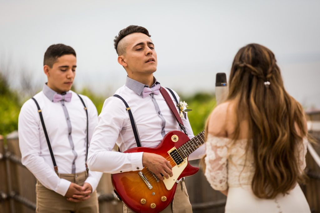 Groom playing guitar and bride singing