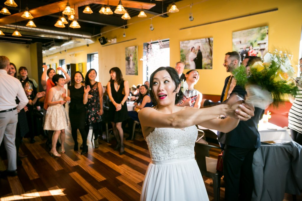 Bride tossing bouquet for an article on bouquet and garter toss alternatives