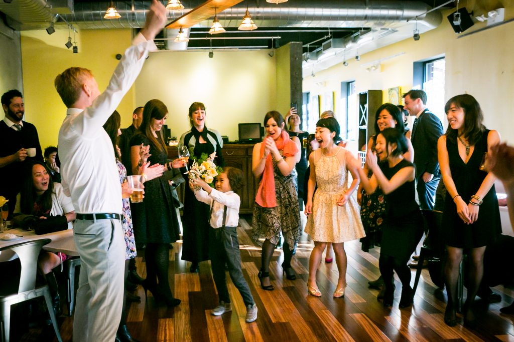 Little boy catching bouquet for an article on bouquet and garter toss alternatives