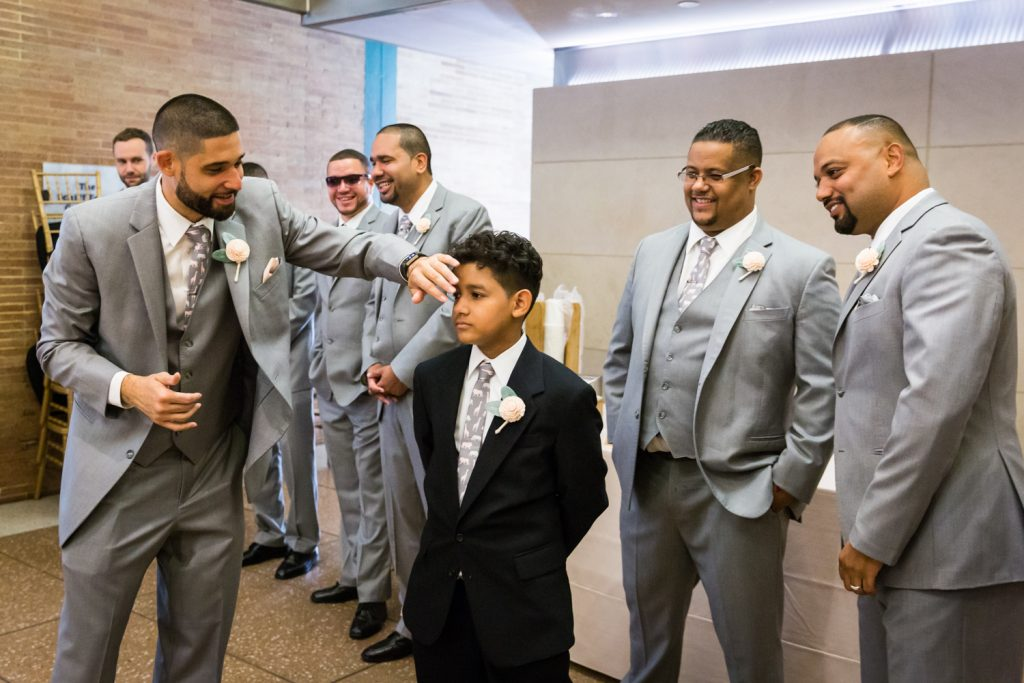 Groomsman fixing boy's hair at a Bronx Zoo wedding