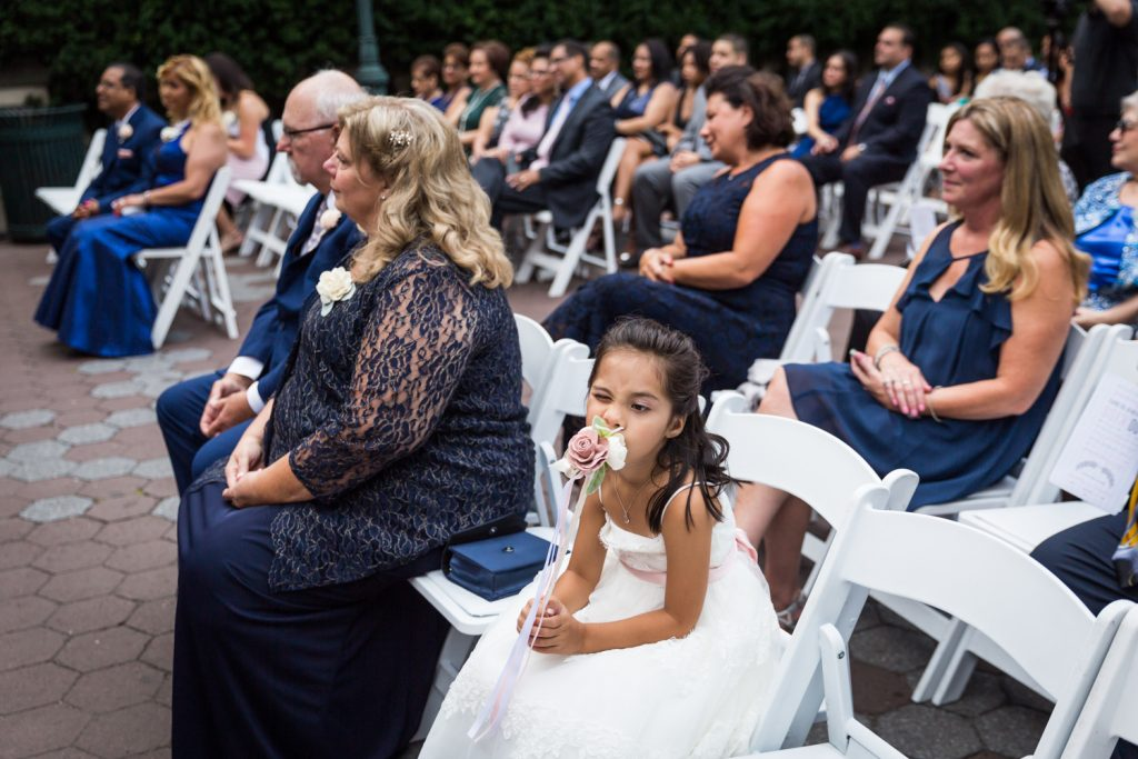 Flower girl smelling bouquet at a Bronx Zoo wedding