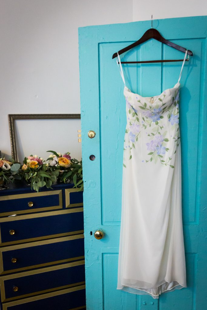 White, floral wedding dress hanging on blue door for an article on the pros and cons of a restaurant wedding
