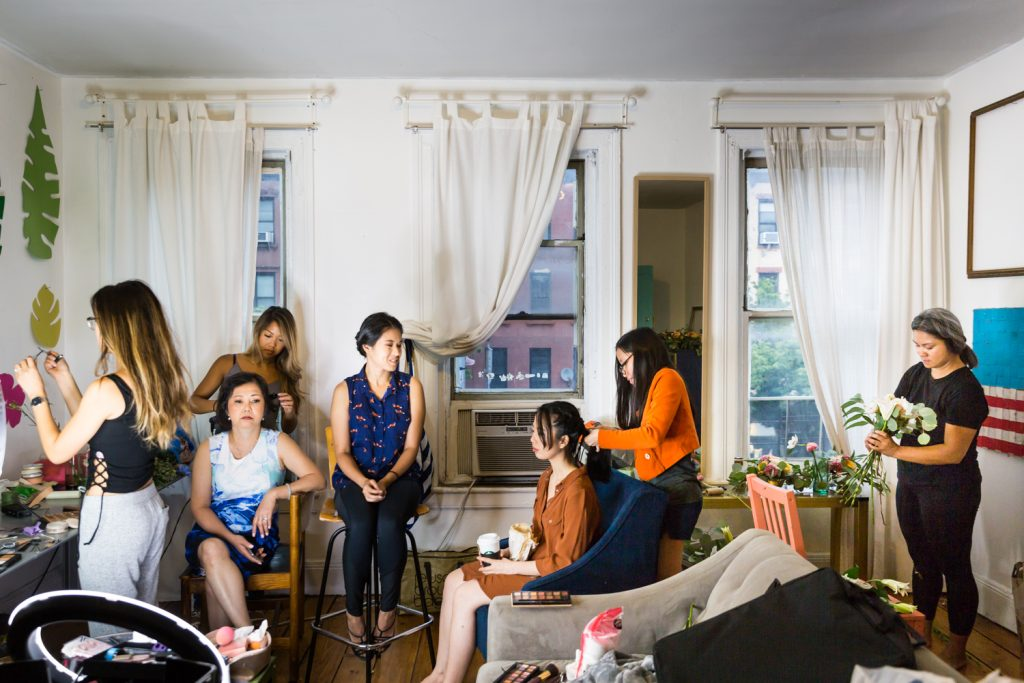 Bride, bridesmaids, and family getting ready in apartment for an article on the pros and cons of a restaurant wedding