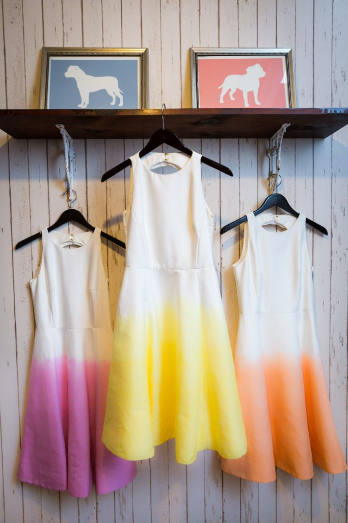 Three brightly colored, ombre bridesmaids dresses hanging from shelf for an article on the pros and cons of a restaurant wedding