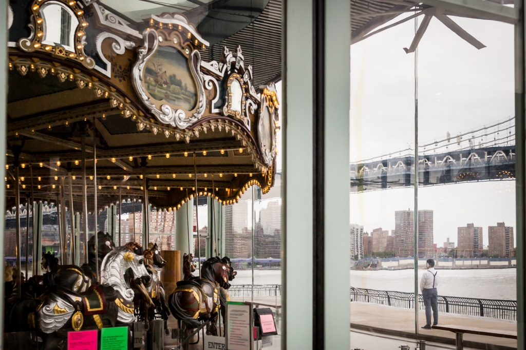 Groom standing behind glass wall at Jane's Carousel for first look
