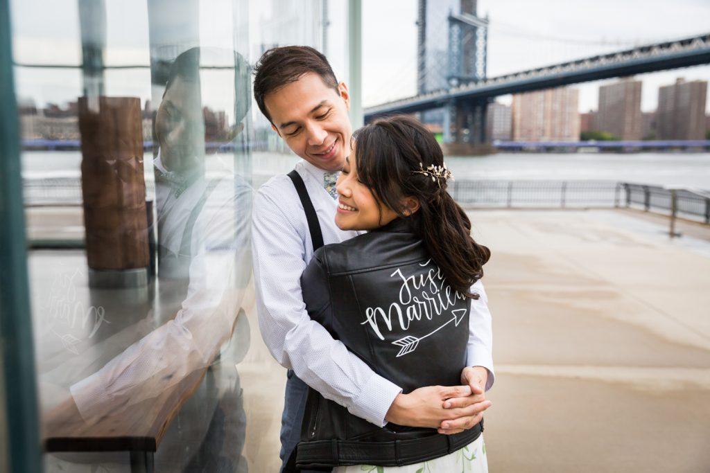 Groom hugging bride wearing 'just married' leather jacket