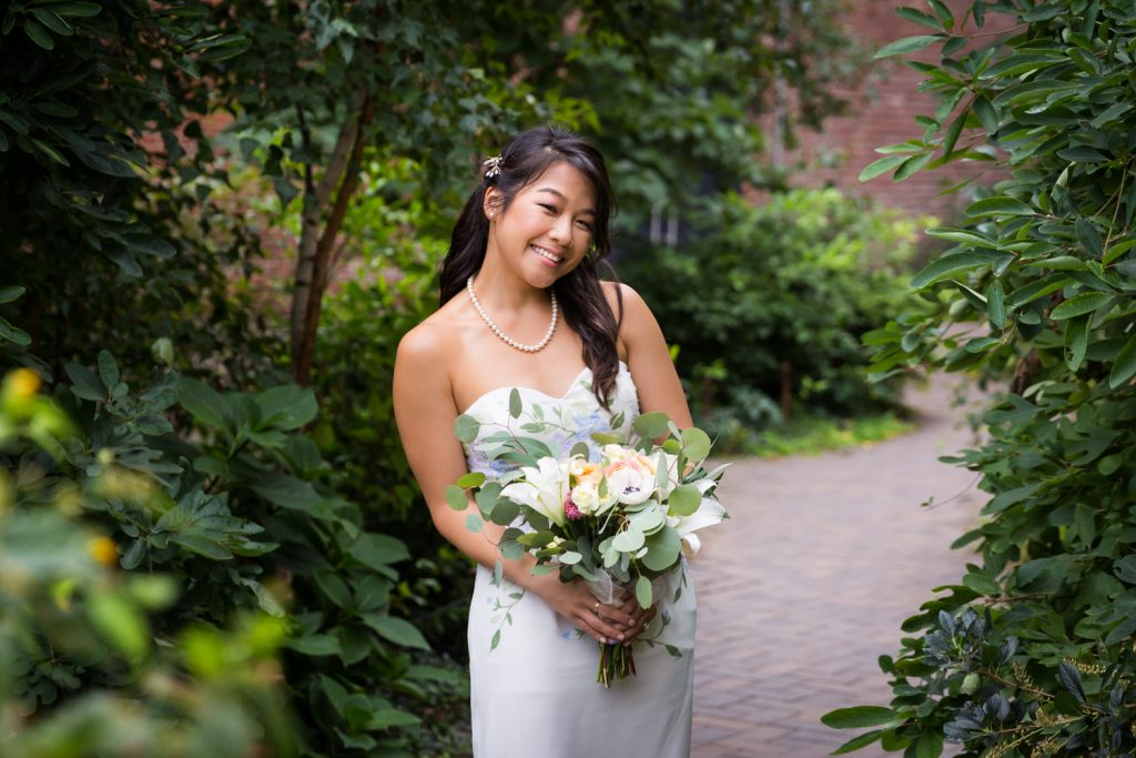 Bride holding bouquet of flowers for an article on the pros and cons of a restaurant wedding