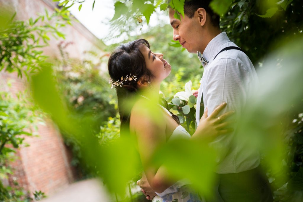 View through leaves of bride and groom looking at each other for an article on the pros and cons of a restaurant wedding