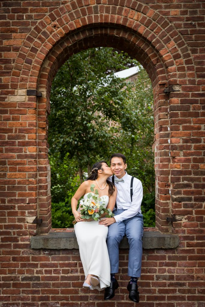 Bride kissing groom on cheek in brick archway for an article on the pros and cons of a restaurant wedding