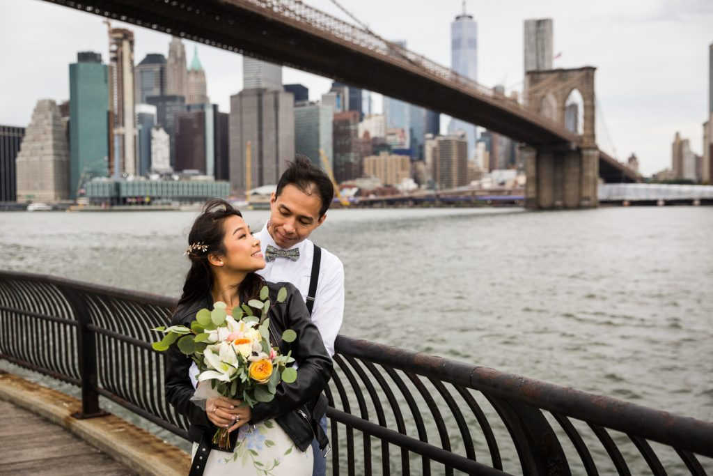 Bride and groom on waterfront with Brooklyn Bridge in the background