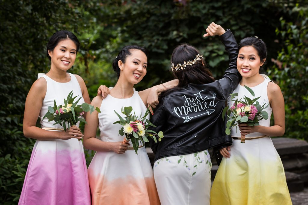Three bridesmaids in ombre dresses and bride in 'just married' leather jacket